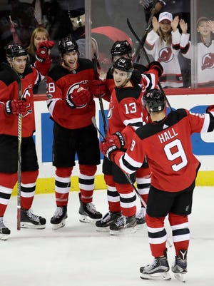 New Jersey Devils players celebrate a goal by Damon Severson, second from left, during the third period of an NHL hockey game against the Ottawa Senators, Friday, Oct. 27, 2017, in Newark, N.J. (AP Photo/Julio Cortez)