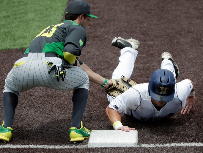 Xavier's Mitch Elliott dives safely back to first base as Oregon first baseman A.J. Balta, left, applies the tag during a pickoff attempt in the third inning of an NCAA college baseball regional tournament game Sunday, June 1, 2014, in Nashville, Tenn. (AP Photo/Mark Humphrey)