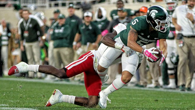 Michigan State Spartans  wide receiver Hunter Rison (5) makes a catch against the Indiana Hoosiers during the second half of a game at Spartan Stadium.