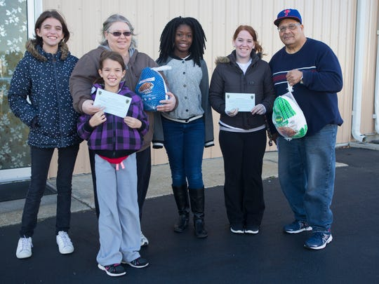 Haidyn Heverinth-Lowe, from left, Harlee Heverin-Lowe, Vickie Heverin, and Stephanie Wood, second from right received turkeys from Gifty Richardson, center, and Frank Richardson with Amazing Grace Chapel after turning their citations for being good citizens from Middletown Police Officers.