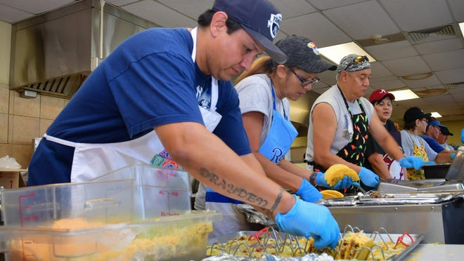 Members of the crew created by the Topeka-based Escobar family, which since 1987 has prepared the food served to those attending the first day of Topeka's annual Fiesta Mexicana, works in the kitchen Tuesday.