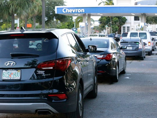 Motorists wait in a line of cars to buy gas at a Chevron