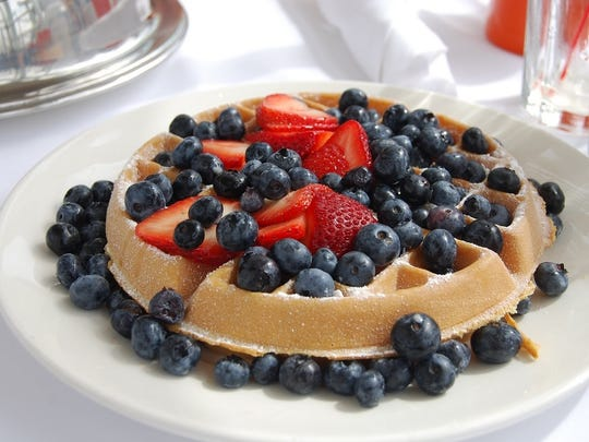 Belgian waffle with blueberries and strawberries at