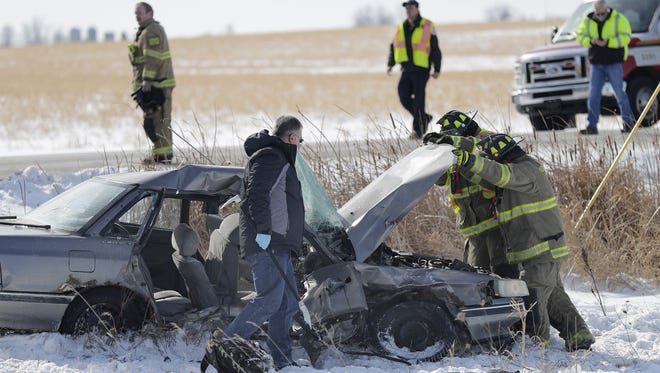 Emergency personnel examine the scene of a two-vehicle crash on Monday near Kaukauna.