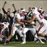 Michigan State's Keith Nichol (center) pushes his way toward the goal line to score a touchdown after catching a tipped pass as Wisconsin's Jared Abbrederis (4) and Mike Taylor (53) defend in 2011 in East Lansing, Mich.