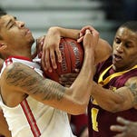 Ohio State's Marc Loving, left, battles for control of the ball with Minnesota's DeAndre Mathieu during Thursday night's Big Ten Conference tournament game.