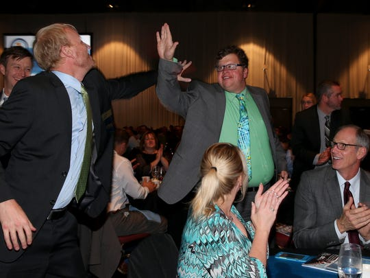 Kevin Schulte high fives Scott Abbett at the Top 100 as SunCommon NY is recognized as the #1 company for 2017.