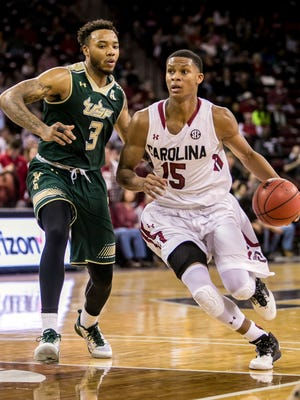 South Carolina guard PJ Dozier (15) drives around South Florida guard Roddy Peters (3) Saturday afternoon in Columbia.