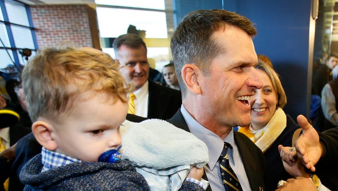 Jim Harbaugh holds his son Jack after a news conference Dec. 30, 2014.
