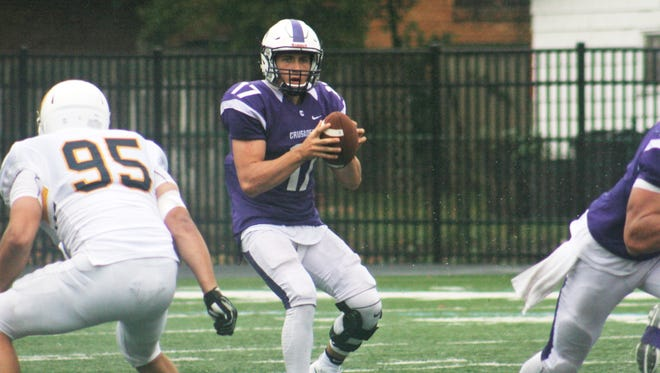 Capital quarterback Thomas Wibbeler takes a snap in Saturday's game against Mt. St. Joseph. The Zanesville alum threw for three touchdowns, including one to former Blue Devil teammate, Dar Stanford.