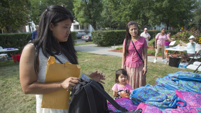 Thet Mary Oo, left, Shen Shen, center, and Pyi Papyieye, of Ithaca, pick out a backpack at Catholic Charities Monday morning.