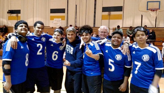 The Virginia School for the Deaf and The Blind's goalball team celebrates after winning the championship at the Eastern Athletic Association for the Blind Tournament on Saturday at the West Virginia School for the Blind in Romney, W.Va. It was the school's first championship in the sport. From left, Daniyal Slman, Sean Walker, Hunter Johnson, head coach Rory Swientek, Tyrone Brotherton, assistant coach Jim Kiser, Malik Sims, Zion Walker.