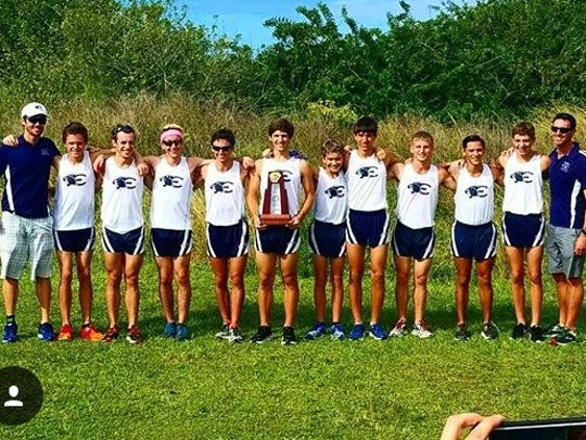 The Estero cross country poses for a picture after winning the Class 3A-District 12 race at Palmetto Ridge High School on Thursday, Oct. 20. Holding the trophy is senior Arye Beck, who won the individual title.