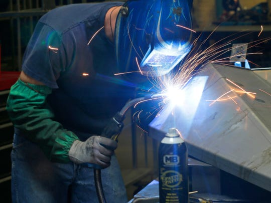 A welder apprentice works on a fender at GenMet in Mequon.