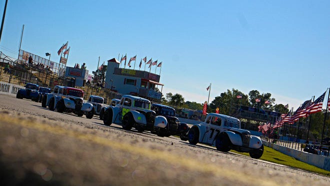 A field of Legends cars races into Turn 1 during a heat race prior to the 2019 INEX Legends Asphalt Nationals at Carteret County Speedway.
