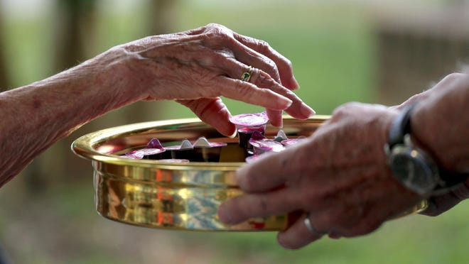 Sealed cups are taken by congregants at Lafayette Street United Methodist Church's outdoor communion on Thursday.