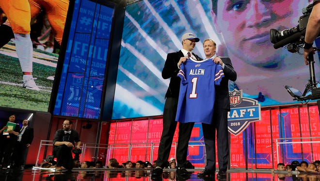 Wyoming's Josh Allen, left, is presented with his Buffalo Bills jersey by Commissioner Roger Goodell during the first round of the NFL football draft, Thursday, April 26, 2018, in Arlington, Texas. (AP Photo/David J. Phillip)