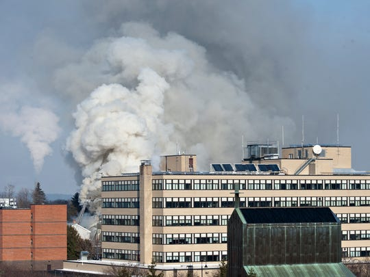 Smoke rises behind the federal building from a blaze at the Free Methodist Church on Elmwood Avenue in Burlington on Thursday, Jan. 15, 2015, as seen from the Burlington Free Press newsroom on Bank Street.