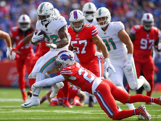 Oct 20, 2019; Orchard Park, NY, USA; Miami Dolphins running back Mark Walton (22) leaps while being tackled by Buffalo Bills strong safety Micah Hyde (23) during the first quarter at New Era Field. Mandatory Credit: Rich Barnes-USA TODAY Sports