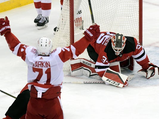 New Jersey Devils goaltender Cory Schneider (35) reacts as Detroit Red Wings center Dylan Larkin (71) celebrates his goal during the third period of an NHL hockey game Monday, Jan. 22, 2018, in Newark, N.J. The Red Wings shut out the Devils 3-0. (AP Photo/Bill Kostroun)