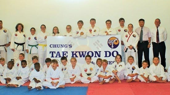 Chung's Taekwondo and Fitness is busy making improvements to its facility. The students are pictured with school owner and head instructor Tracy Daar and American Taekwondo Foundation's own ninth-degree Grand Master Y.S. Chung. Chung's TKD hosted a fundraiser Saturday in the form of a yard sale and cookie/brownie sale in front of the TKD building located at 304 King Street in Tallassee.