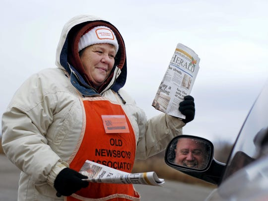 Lisa Towle, of Kimball Township, sells a paper to Gary Moutoux, of Port Huron, for the Old Newsboys fundraiser at the Port Huron Factory Outlets in Kimball Township. Towle first volunteered with the Old Newsboys when she was 12.
