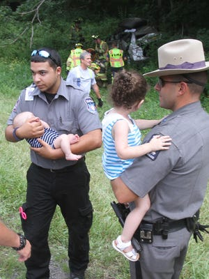 An EMStar paramedic and New York State trooper hold a 2-month old infant and a 2-year toddler as Brewster firefighters extricate their mother from a vehicle that rolled over on westbound Interstate 84 in the town of Southeast Aug. 6,  2016. The two children were in carseats and not seriously injured, while their mother was seriously injured in the 2:30 pm accident. The westbound lanes of I-84 were shut down as firefighters worked at the scene. Mother and children were transported to Danbury Hospital.