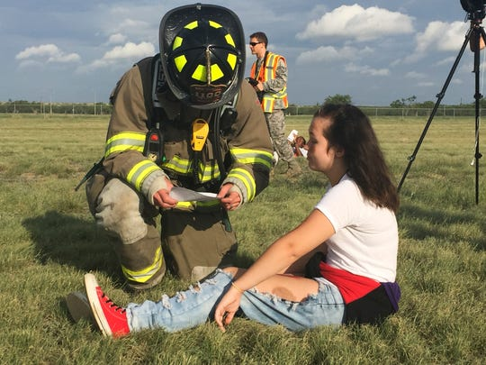 Firefighter Shane Mathews assists volunteer 'victim' Kimberlee Miller at emergency preparedness training Thursday, July 13, 2017, at San Angelo Regional Airport.