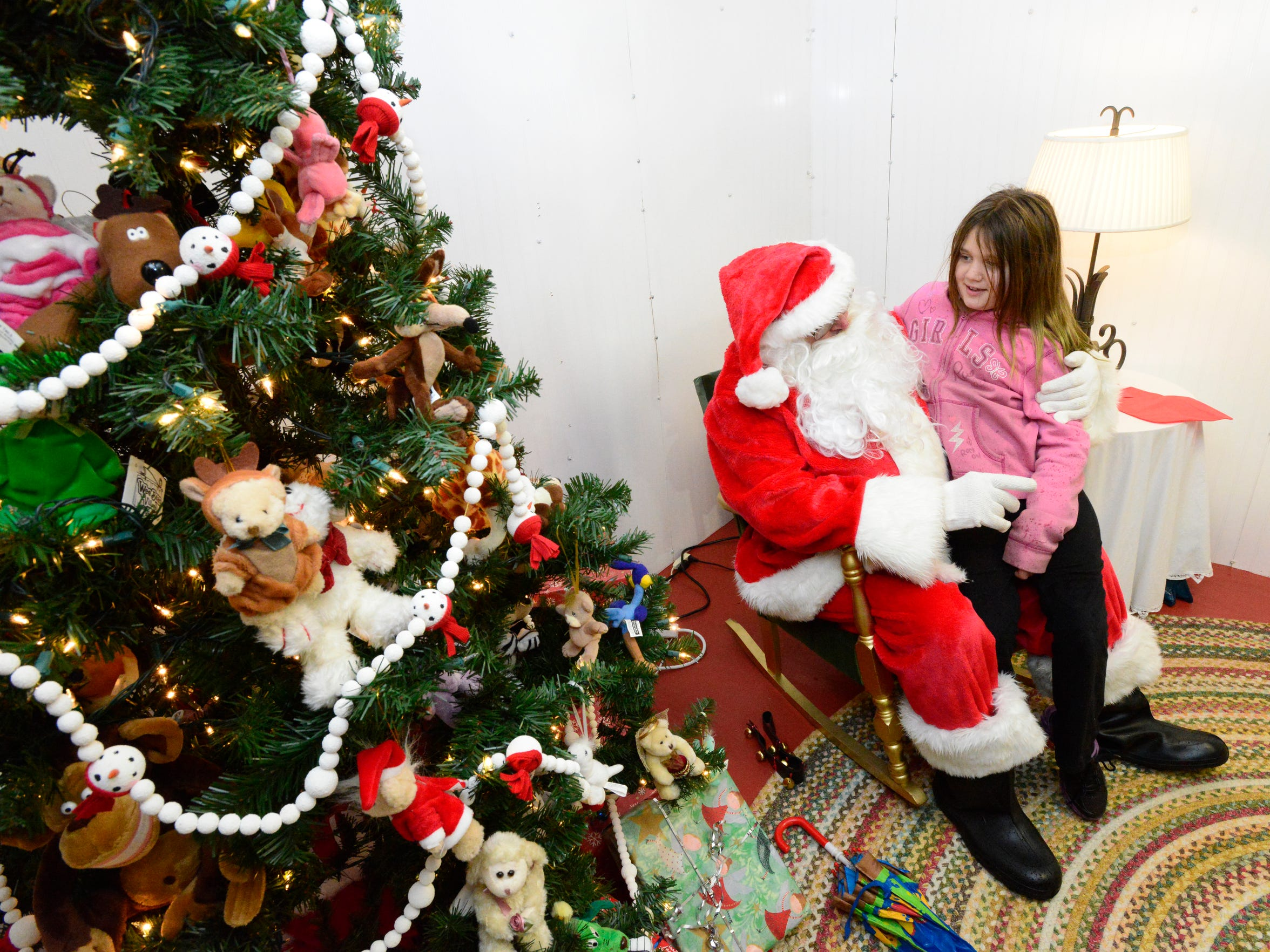 Kimberly Weber, 9, of Fremont, tells Santa she wants a remote control Optimus Prime Transformer for Christmas.