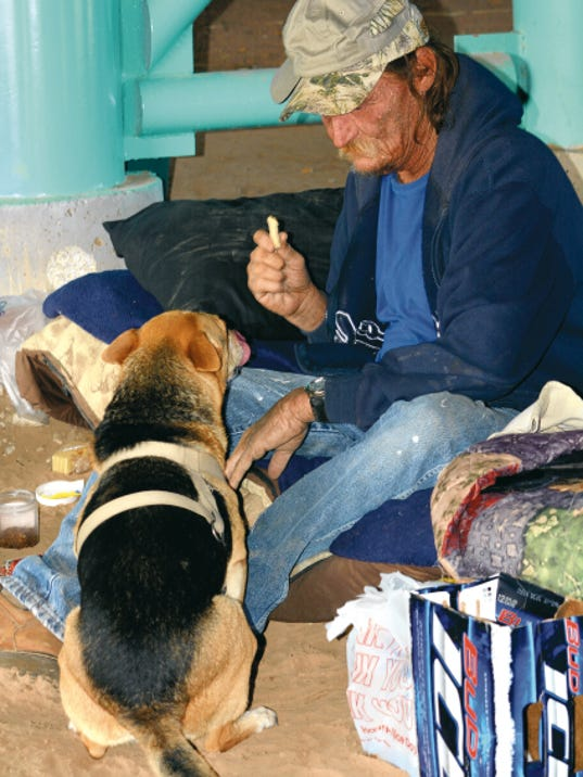 """Matt Hollinshead — Current-Argus Roy Alldredge, 63, gives """"Girlfriend"""" a dog treat at one of the undergroup homeless camps on Saturday. Alldredge said he didn't know what to name her at first. He then explained that because she's female and a friend, he decided to name her """"Girlfriend."""""""