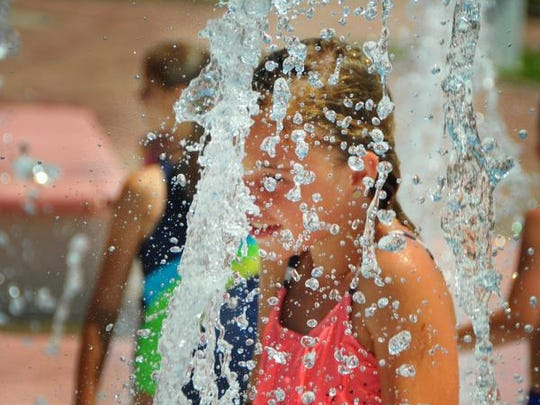 Kelly Monteleone, 8, plays in the fountain at Riverfront Park in Cocoa during a hot summer day in this 2015 file photo.