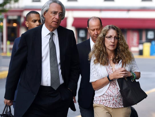 Attorney Tom Kline, left, walks with the parents of