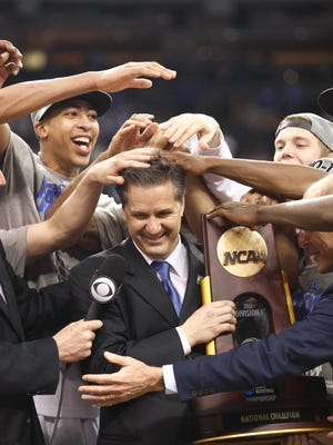 Kentucky players mess up coach John Calipari's hair while he accepts the National Championship trophy. Apr. 2, 2012