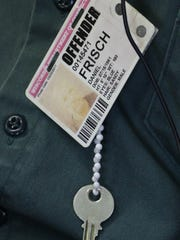 Daniel Frisch wears an ID tag and a key around his