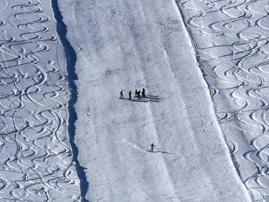 Skiers make their way down a groomed slope during opening