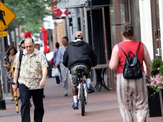 Cyclist Thomas Wiggins, of Wilmington, rides on a sidewalk to avoid traffic on North Market Street on Thursday. A city plan seeks to make the community friendlier to cyclists.