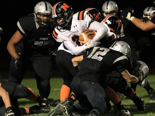 Northville quarterback Justin Zimbo (middle), a thorn in Plymouth's side all night, runs through the line. Trying to tackle him are Michael Jordan (left) and C.J. Wieloch.