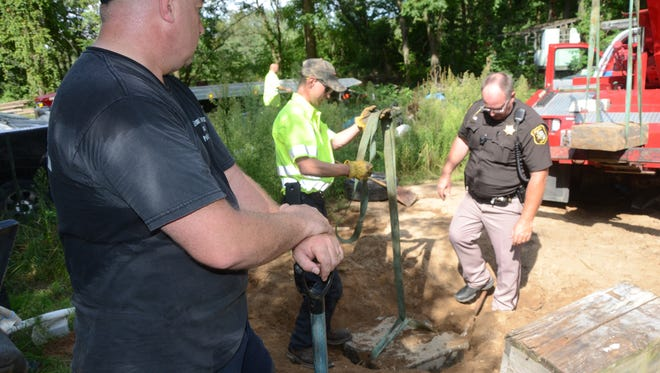 Investigators prepare to lift a stolen headstone from the ground Thursday, Aug. 17, 2017.