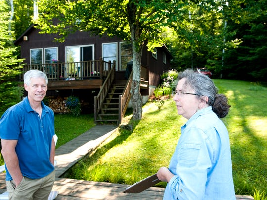 Susan Warren of the Department of Environmental Conservation visits with John Hollar at his camp on Peacham Pond on Tuesday July 8, 2014.