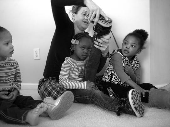 Kelly Gibbons tries to get her daughter Alleeyah ready for school while Mahlany and Kylee watch