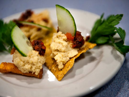 An appetizer of hummus on sweet potato chips with roasted red pepper and olive tapenade is the creation of Chef Tom McGovern of Ladder 24-C at the Erlton firehouse. McGovern has a $7 per head budget, so he uses ingredients like pancake mix in his fresh berry clafoutis with creme anglaise (below).