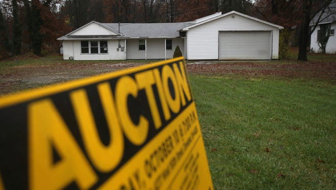 An auction sign stands in front of a foreclosed house in Warren, Ohio.