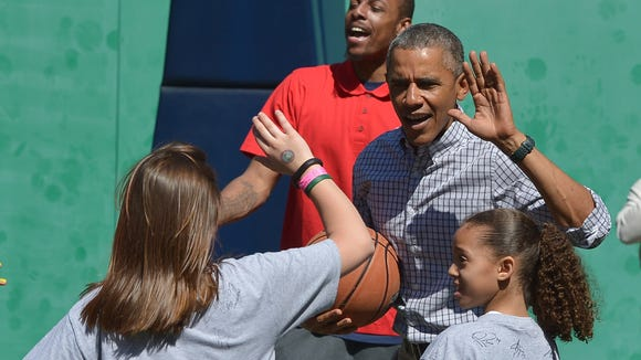 "President Obama ""high-fives"" a child while playing"