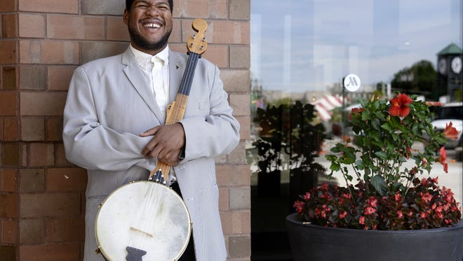 "Young traditionalist musician Jerron ""Blind Boy"" Paxton laughs in East Lansing Friday, where he will be a featured performer at the Great Lakes Folk Festival."