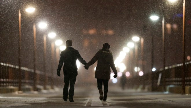 Peter Best and Mackenzie Kuhl hold hands while walking across the Stone Arch Bridge, Monday, Dec. 28, 2015, in Minneapolis.