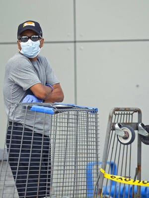A men wearing gloves and a protective mask waits in line to enter the Walmart Supercenter in Miami.