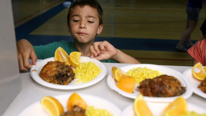 Alex Stevens eyes his lunch at the Boys and Girls Club on Tuesday, July 14, 2015, in Salem. There's no free school lunches during the summer, so the USDA's Summer Food Service Program tries to close that gap by reimbursing meals offered to all kids throughout the summer. Locally the Boys and Girls Club is one of the organizations that partners with the USDA.