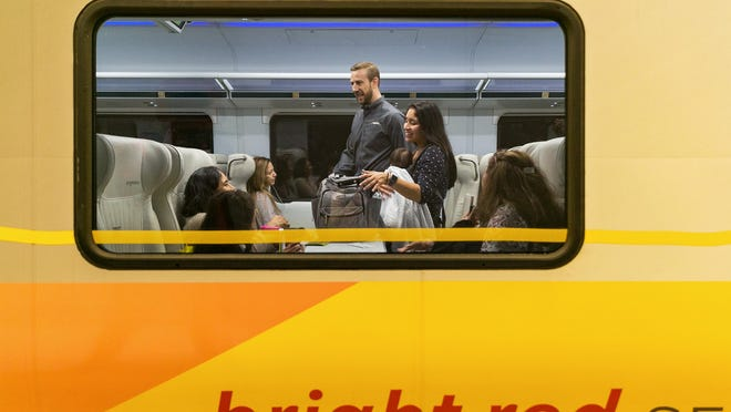 Brightline President and COO, Patrick Goddard walks through the train car greeting passengers leaving Miami to Fort Lauderdale and West Palm Beach on the first day of service for the route, May 19, 2018.