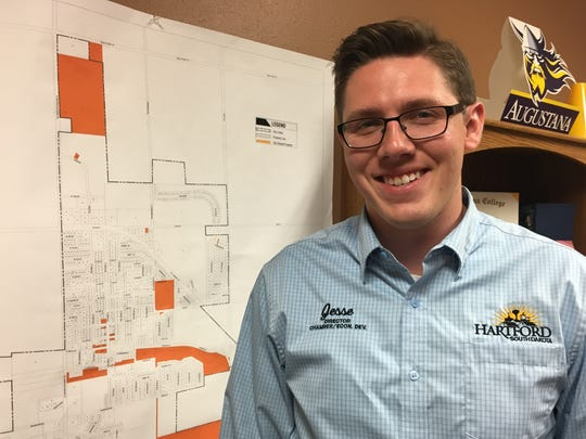 Jesse Fonkert, the chamber and economic development director for the City of Hartford, stands in front of a map in his office showing some of the new developments in the growing city.