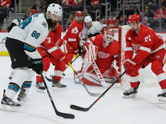 San Jose Sharks defenseman Brent Burns (88) takes ascot against Detroit Red Wings center Dylan Larkin (71) and Red Wings goaltender Jonathan Bernier (45) during the first period of an NHL hockey game Tuesday, Dec. 31, 2019, in Detroit. (AP Photo/Duane Burleson)